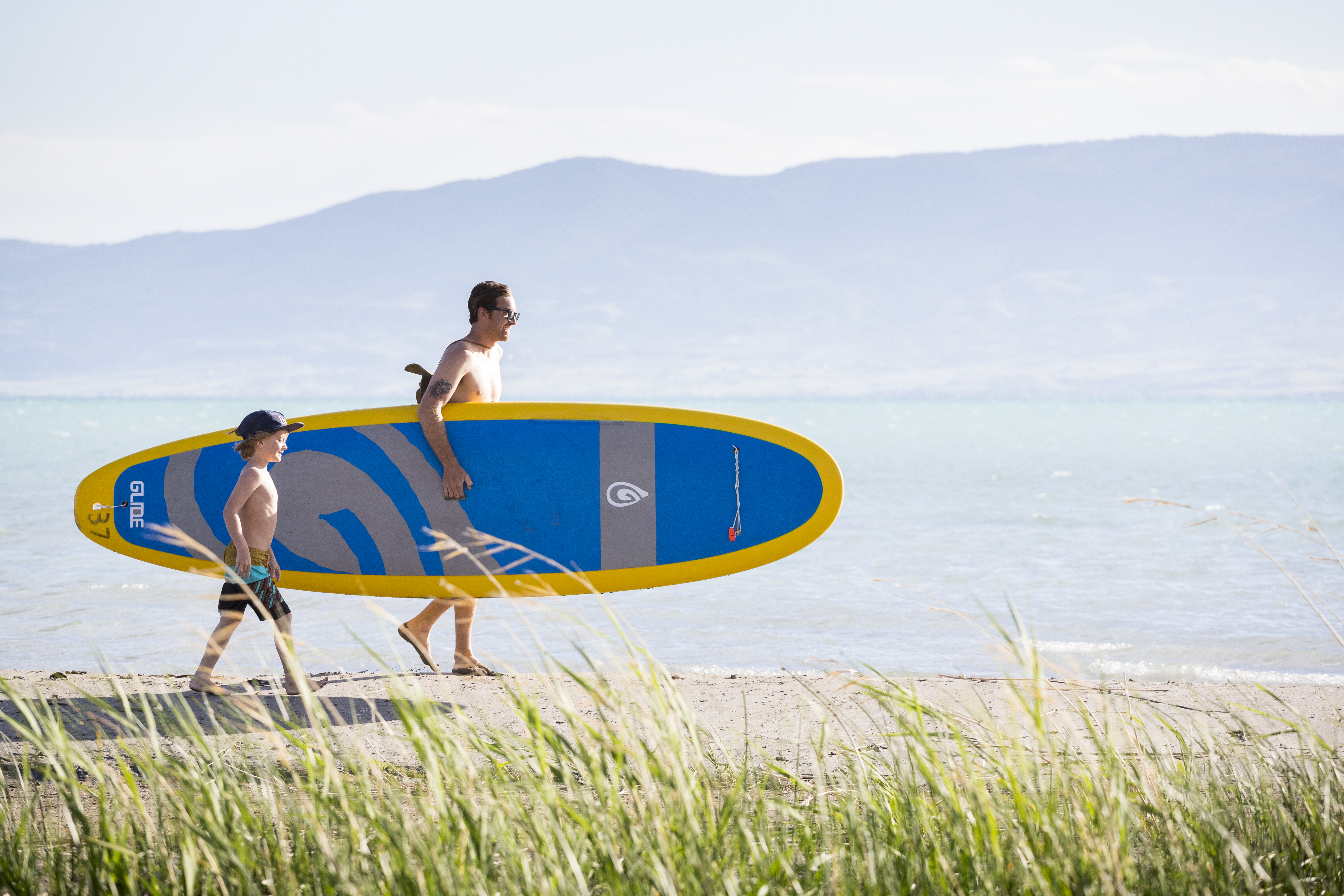 A father and son walking to the lake with their paddle board.