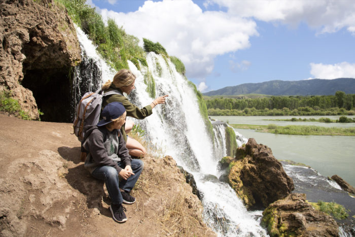 A mother showing her son a waterfall.