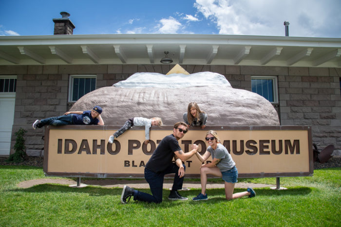 A family taking a family photo in front of the Idaho Potato Museum.