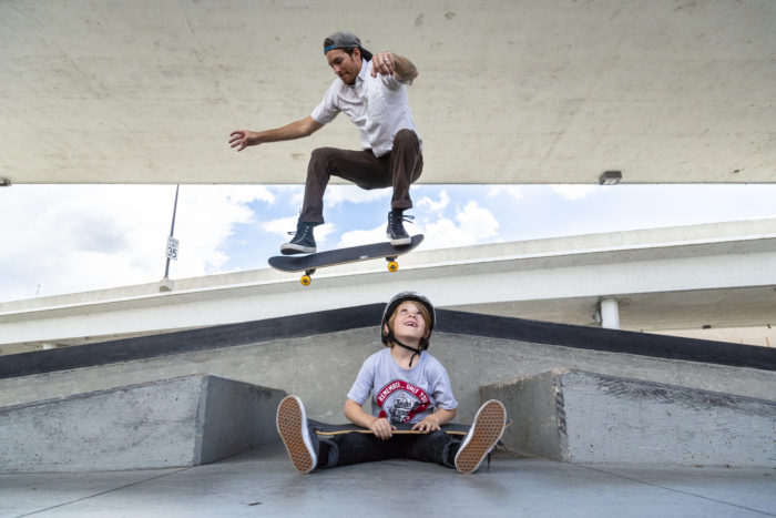 A father jumping over his son at a skate park.