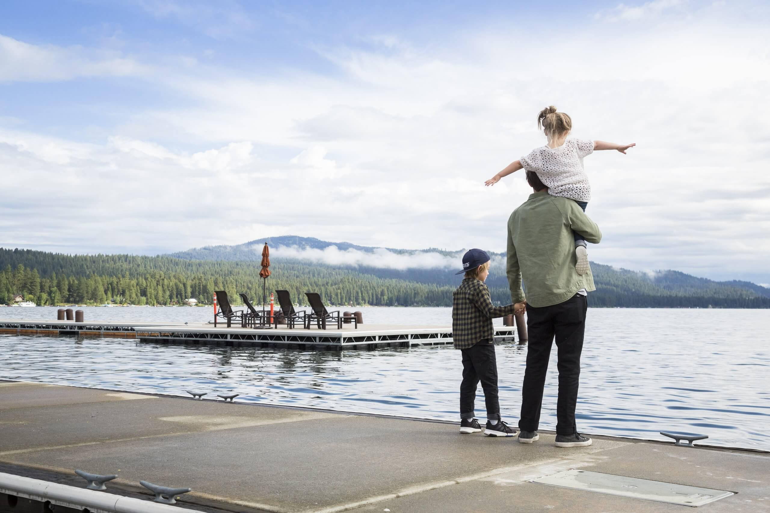 A father holding his child on the dock on Payette Lake.