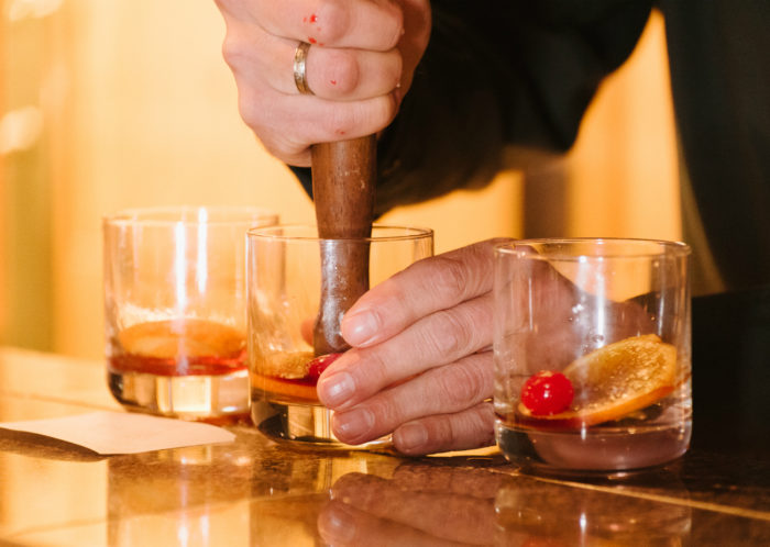 person making cocktails