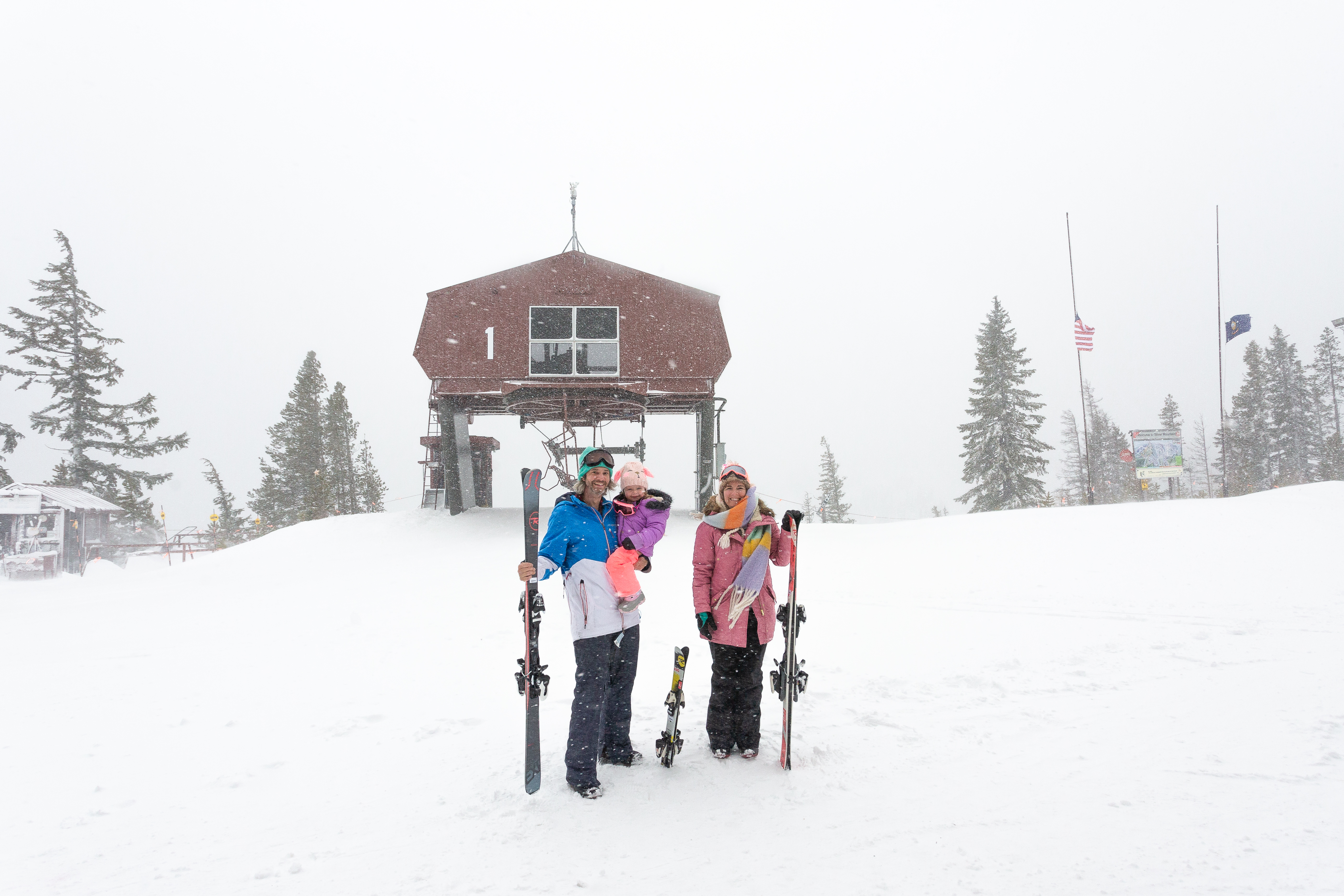 family at top of ski hill with skis