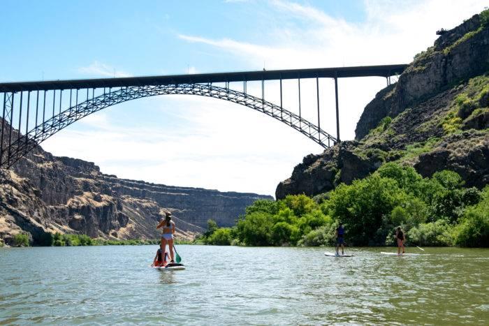 paddleboarder near bridge