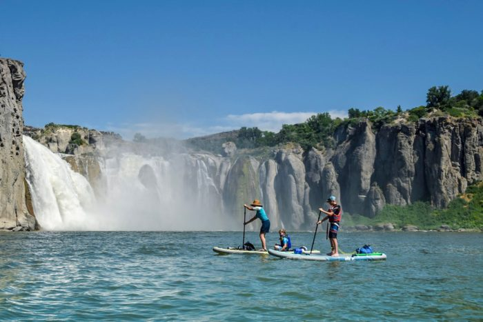 paddleboarders by waterfall