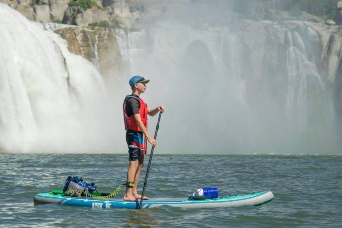 paddleboarding by waterfall