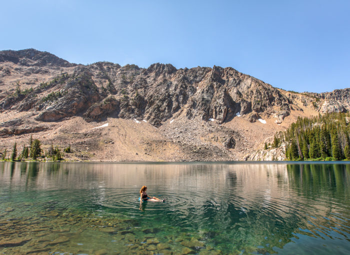 mountain lake with woman in water