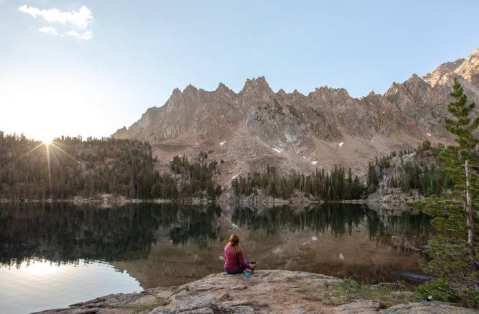 woman sitting at high mountain lake