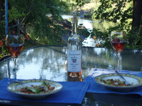 A table outsite along the river with dinner and a bottle of Frenchman's Gulch wine.