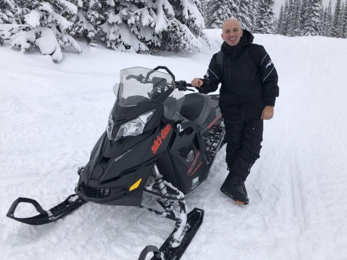 man next to snowmobile