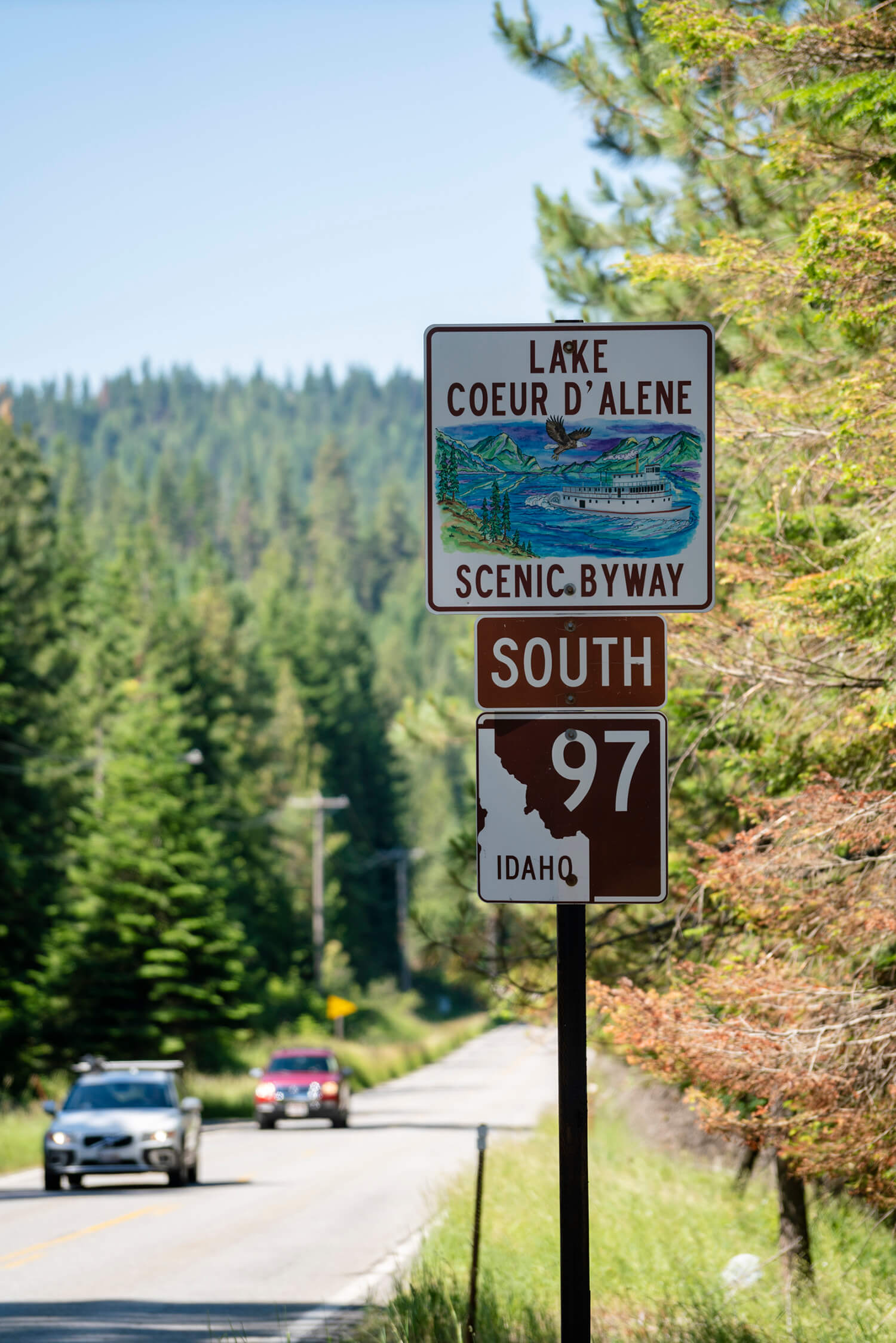 road signs indicating Lake Coeur d'Alene scenic byway and Idaho state highway with two cars driving along the tree-lined byway in the background