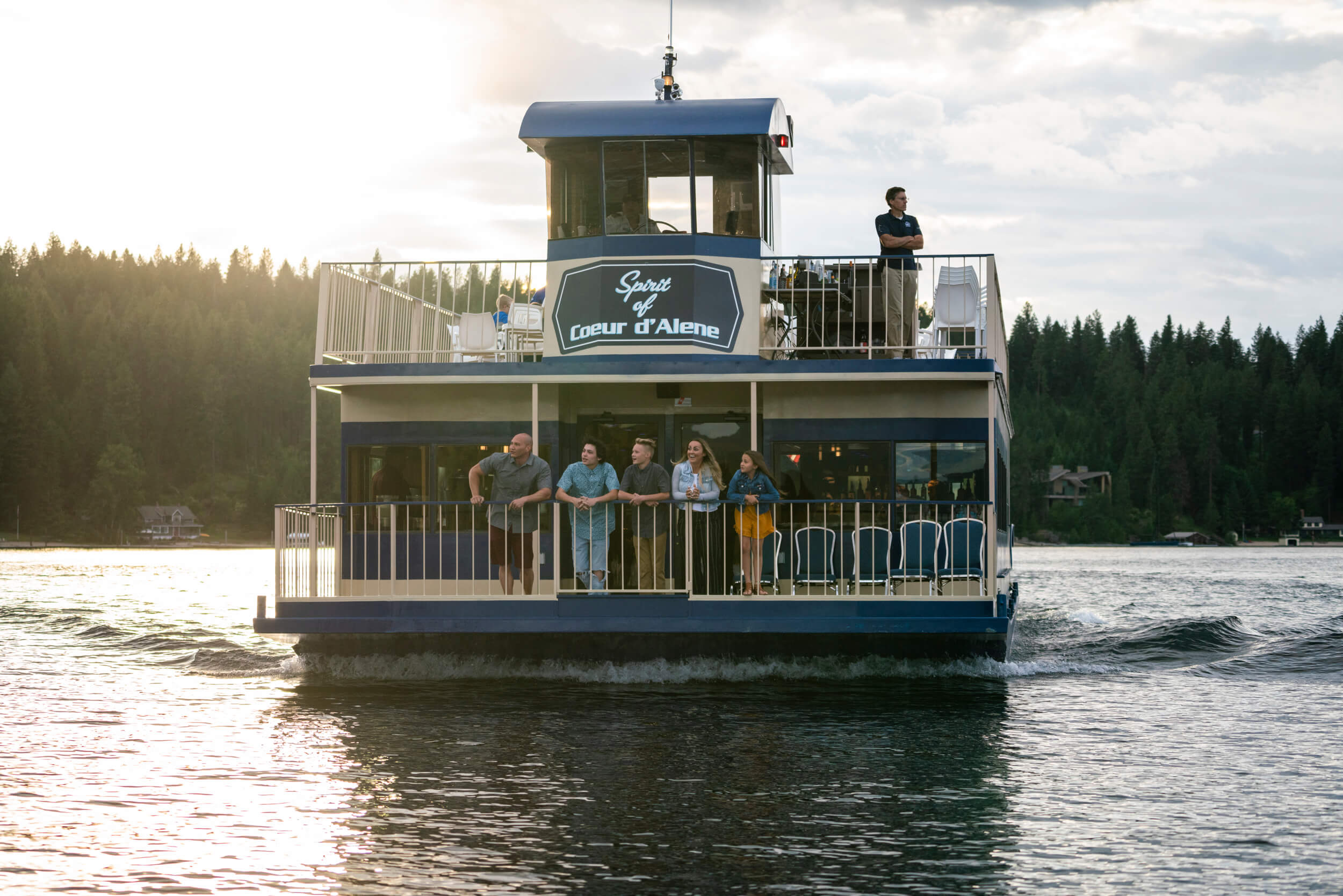 five people leaning on the rails of a Coeur d'Alene Cruise Ship on Lake Coeur d'Alene in Idaho