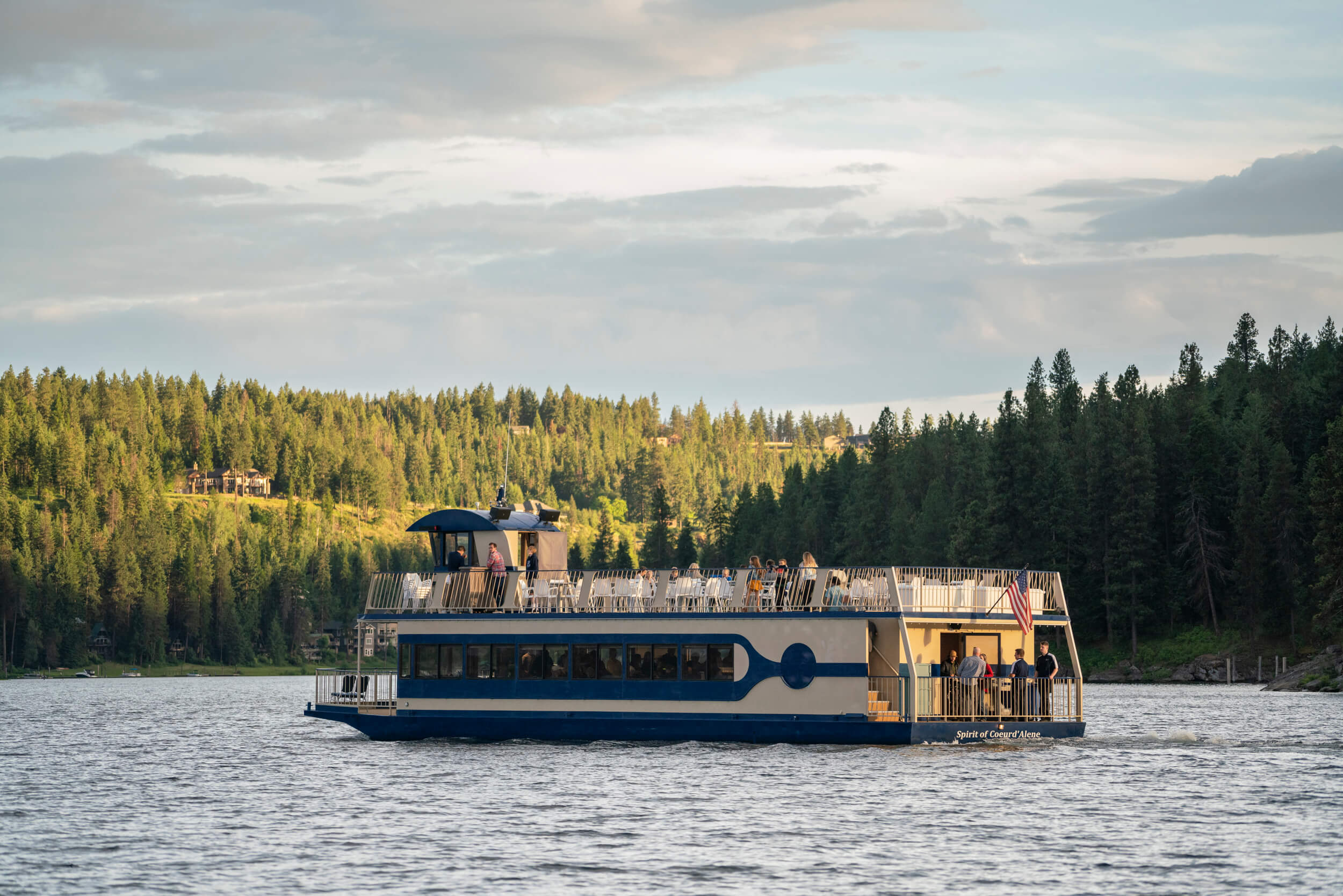 CDA Cruise ship with passengers on Lake Coeur d'Alene surrounded by trees