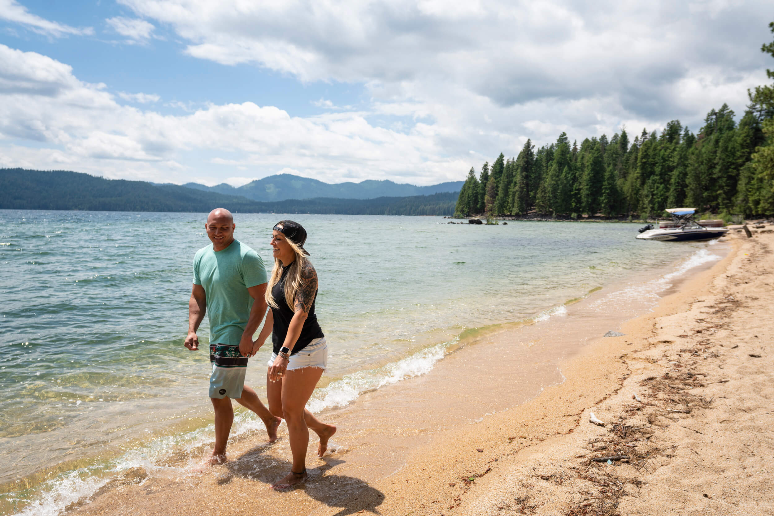 A couple holds hands and walks along the shore of Priest Lake in Idaho