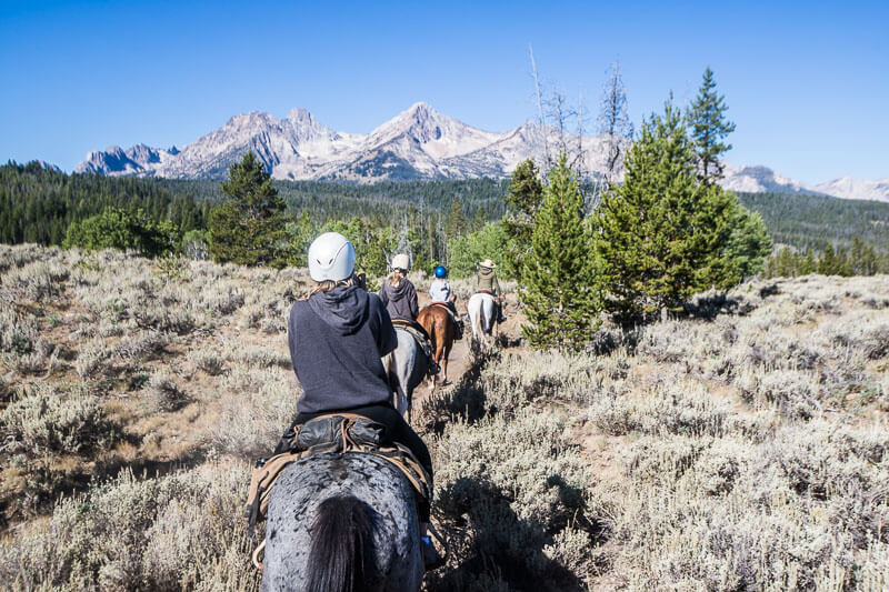 horse back riders on mountain trail