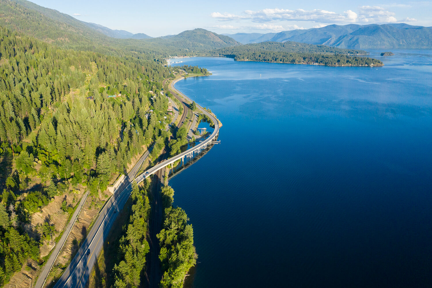 scenic byway curving away from tree-covered mountain and over Lake Pend Oreille