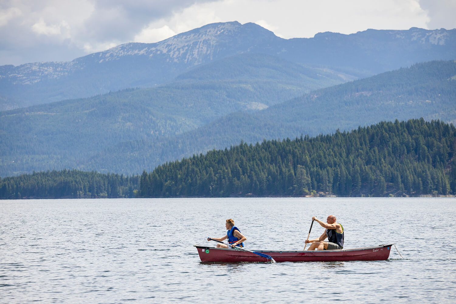 two people paddling a canoe on Priest Lake with tree covered mountains in the background