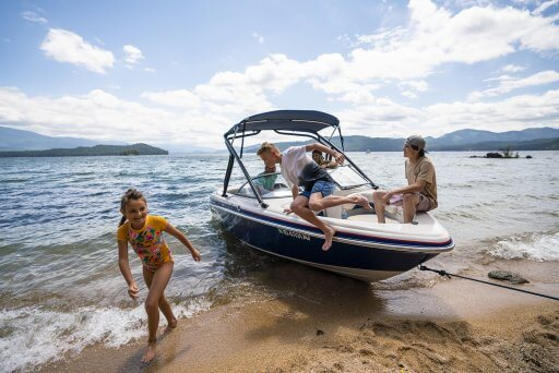 three kids jumping out of a speedboat docked at Priest Lake's beach