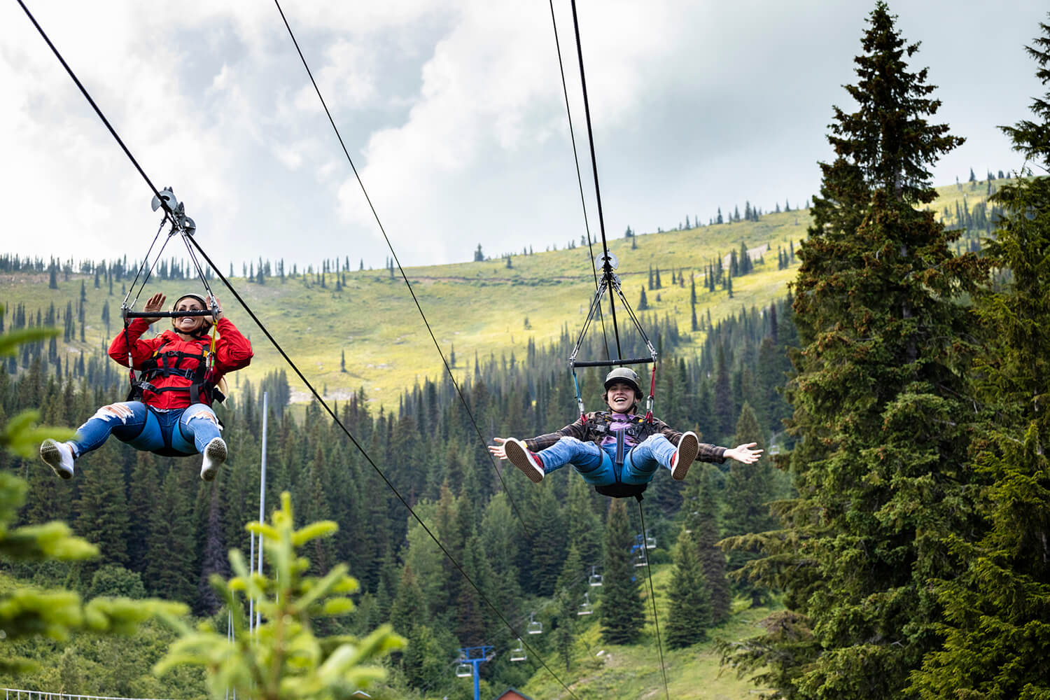 two girls ziplining side-by-side down a tree covered mountain at Schweitzer Mountain Resort