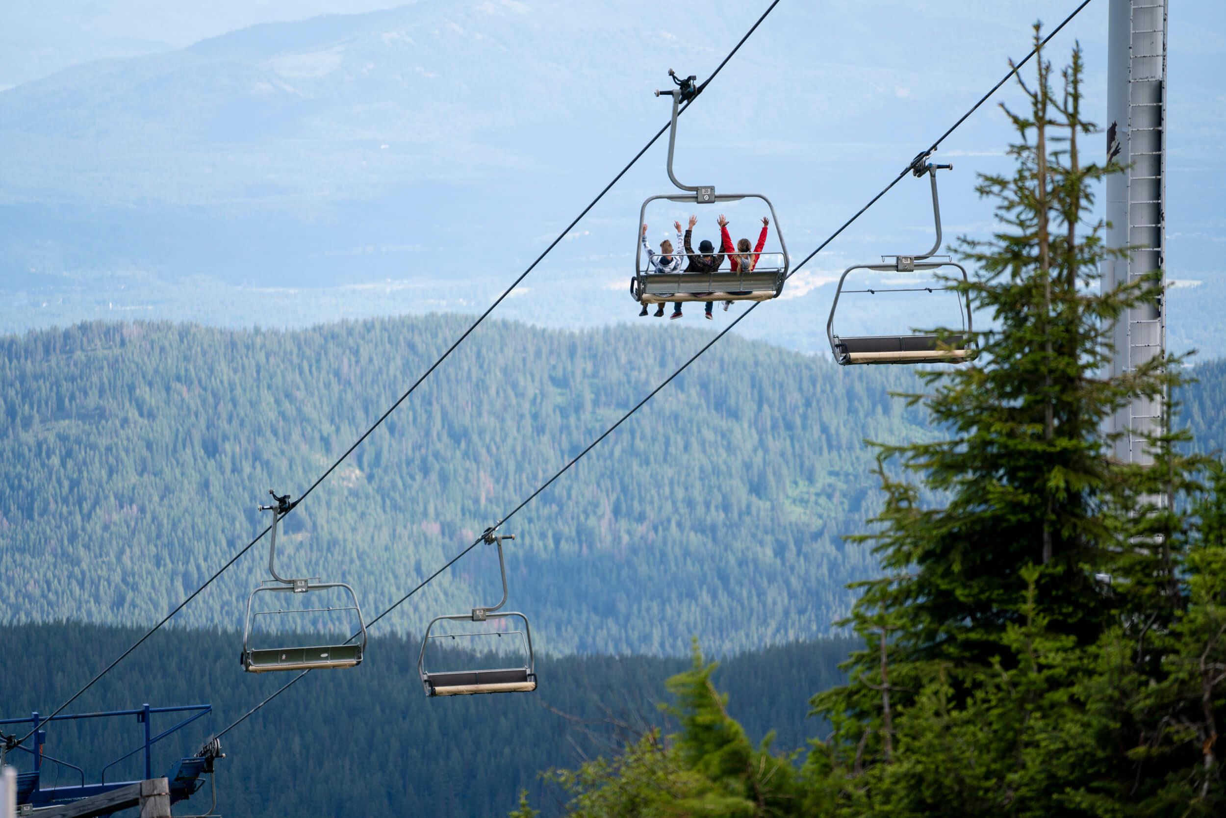 three people with their hands in the air on a ski lift riding over the green mountains at Schweitzer Mountain Resort