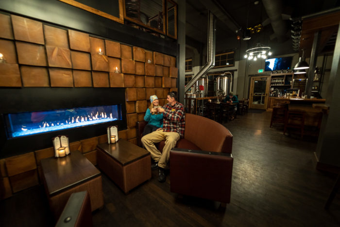 a couple sitting in front of a fire place