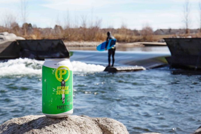 can of beer on a rock by a river