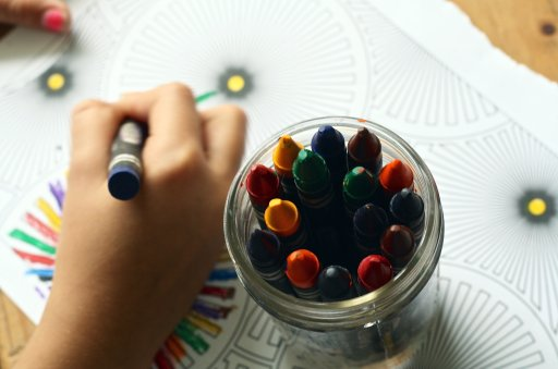 top view of a glass jar of crayons sitting on top of a coloring sheet and a child's hand holding a crayon