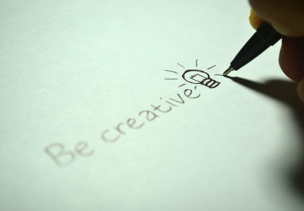 closeup of a hand holding a pen to paper and drawing a lightbulb beside the words be creative