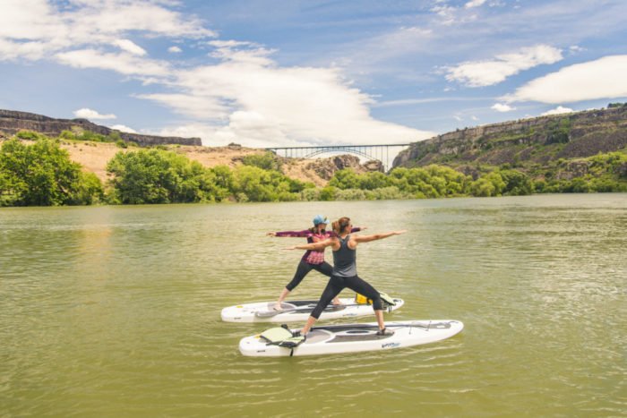 Two women practicing yoga on stand-up paddleboards on smooth river with blue skies, canyon walls and an arched span bridge in the distance.