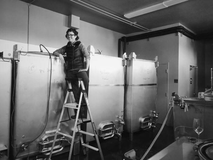 woman on ladder next to wine fermentation tanks