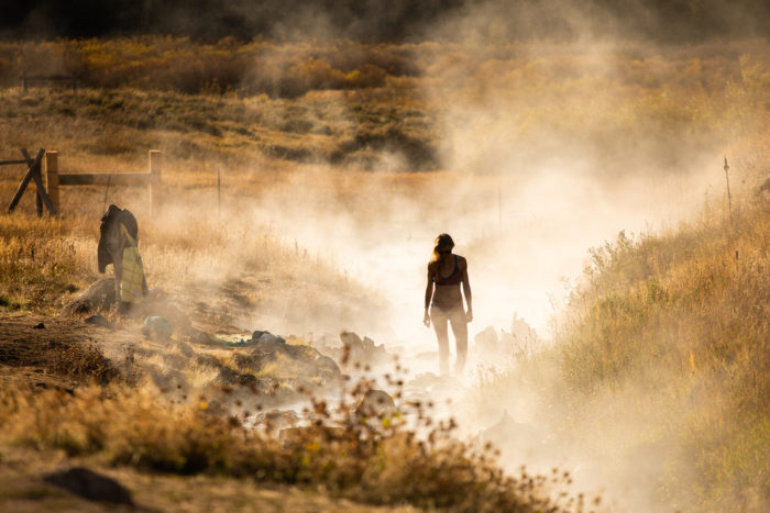 woman standing in steam of hot spring
