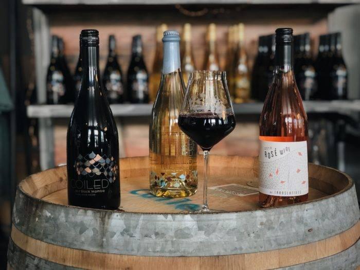 wine bottles and glasses on wine barrel