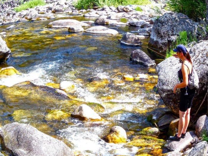 woman fishing in mountain stream