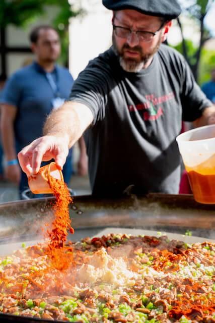 man seasoning paella