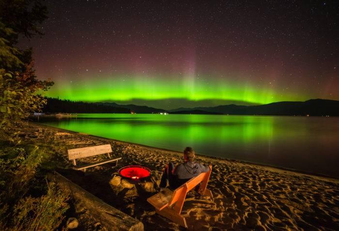 man sitting on beach watching northern lights at Hill's Resort