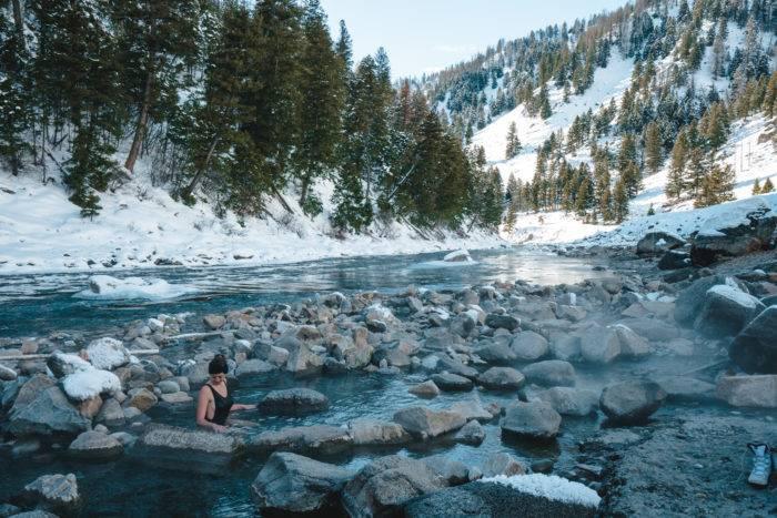 woman in snowy riverside hot spring