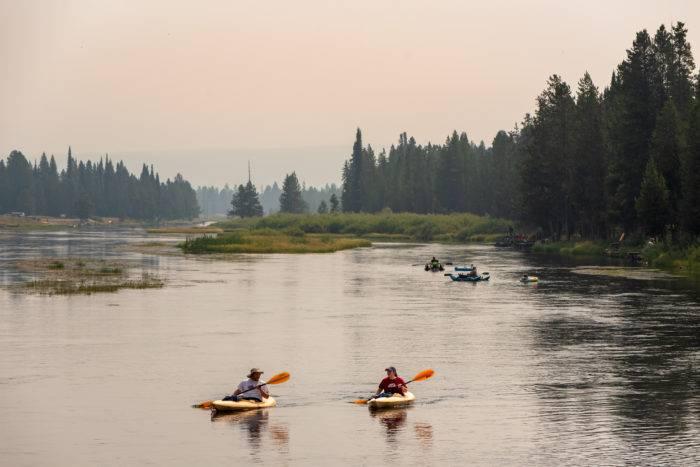 people kayaking down river