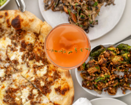 pizza, cocktail, and brussel sprouts on a table