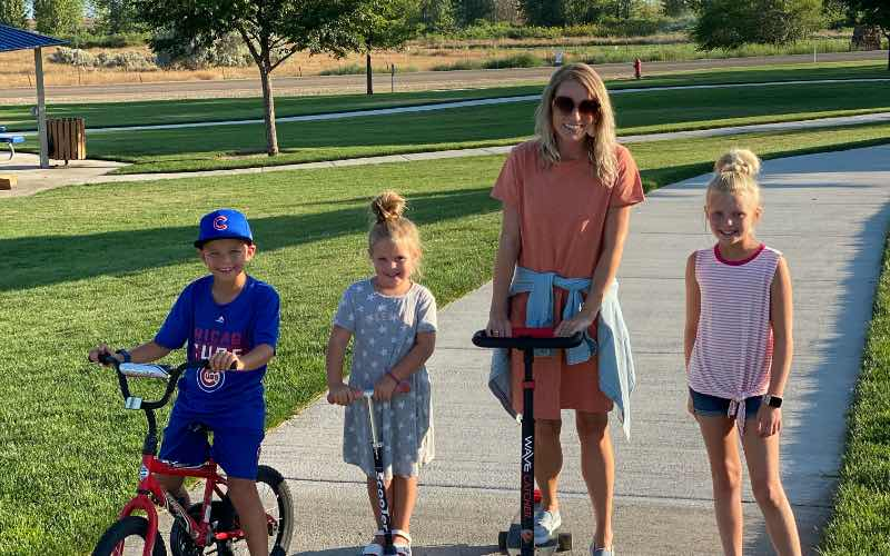 woman and three children riding bikes and scooters at Mallard Park