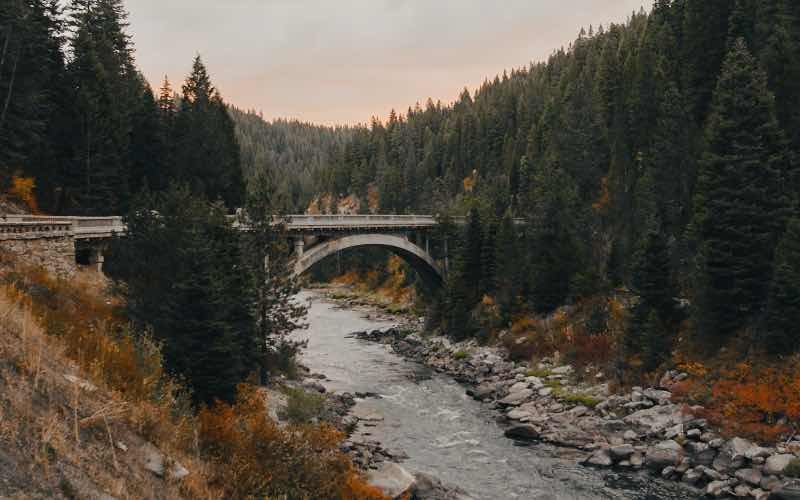 side view of a bridge spanning across a tree-lined river during the fall