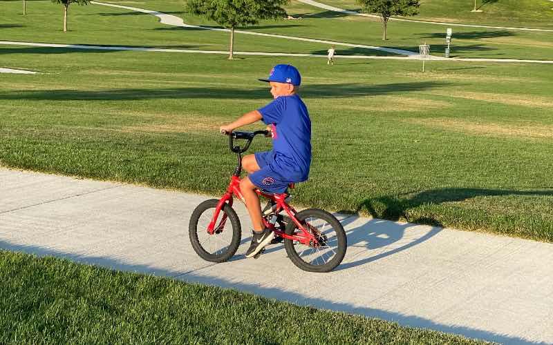 boy riding a bike on a walking path at Mallard Park