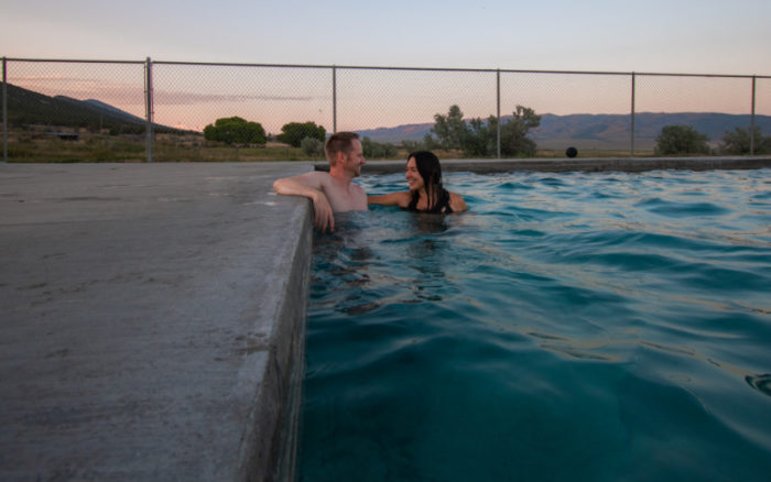 man and woman in an outdoor pool lined by a metal fence and trees and mountains in the background