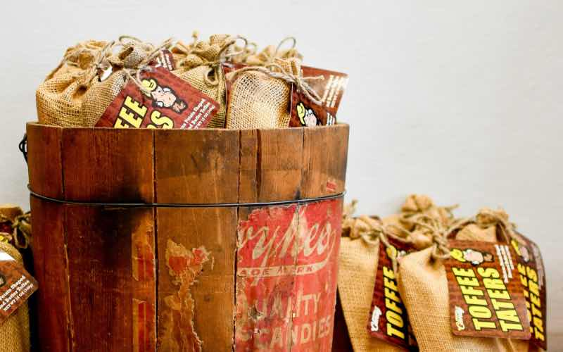 wooden bucket filled with small burlap bags of Toffee Taters candy