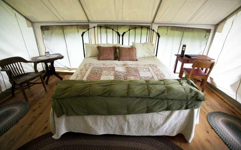 inside of a luxury tent, a bed in the center of a wooden floor along with rugs, small tables and chairs