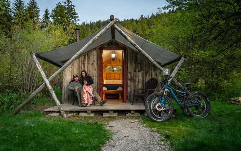 man and woman sitting on a porch in front of a glamping cabin with two bikes leaned against the front of the cabin and trees in the background