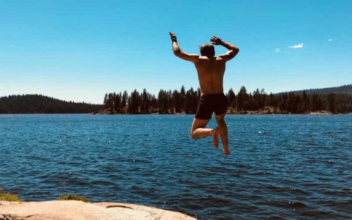 man wearing swim trunks jumping into a lake and a forest of trees in the distance