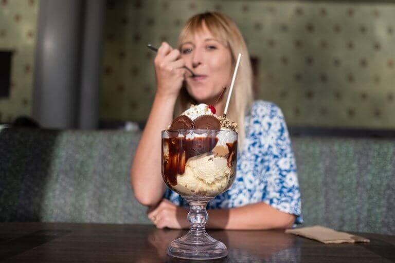 woman eating a large ice cream dessert