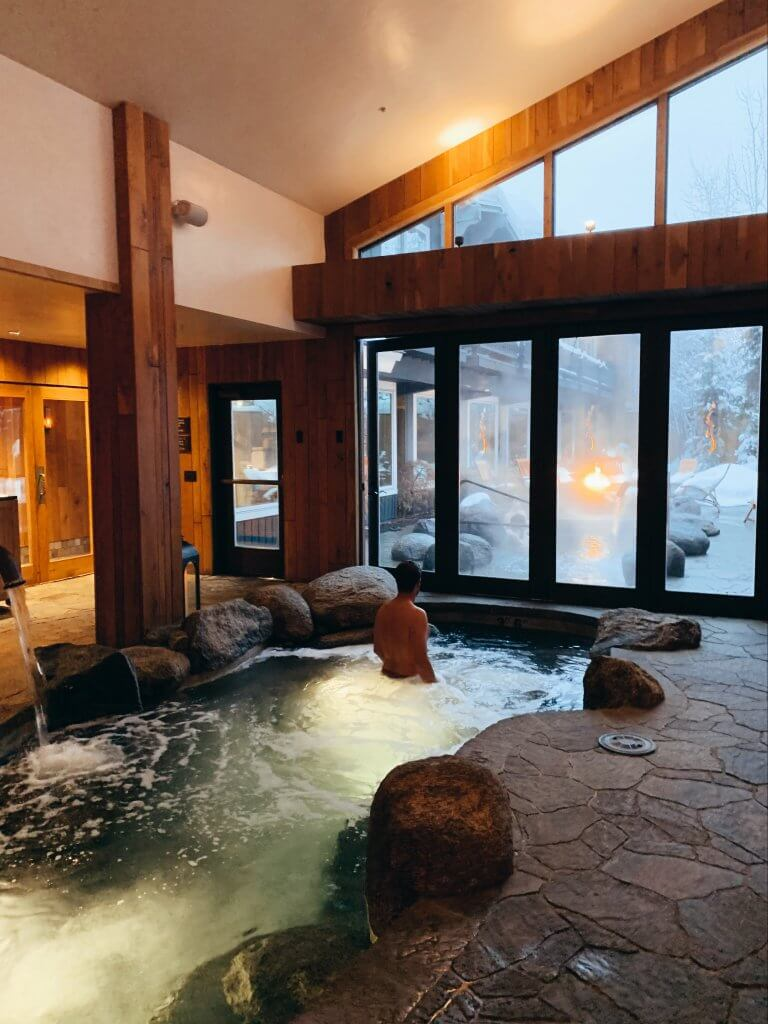 man in spa space enjoying pool while looking at snow
