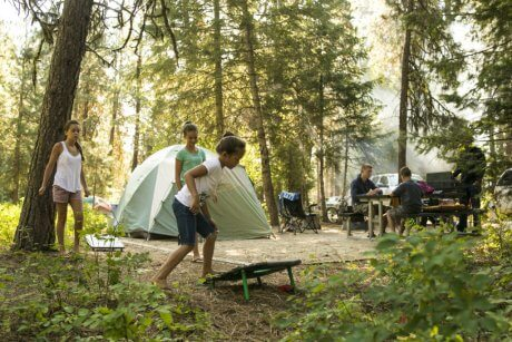 Three children play around their campsite, with tall trees and a sage green colored tent, and white pick up truck in the background.