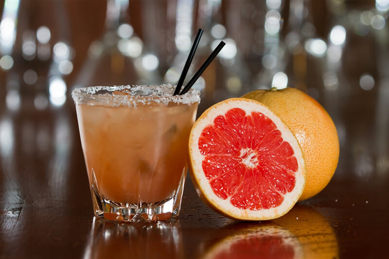 orange colored cocktail with two straws and half a grapefruit leaning against the glass, and a whole grapefruit in the background